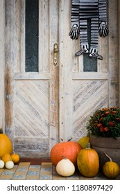 Halloween decorated front door with various size and shape pumpkins and skeletons. Front Porch decorated for the Halloween season.