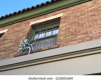 Halloween decoration of artificial human skeleton on a house wall