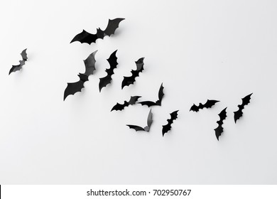 halloween and decoration concept - black paper bats flying over white background