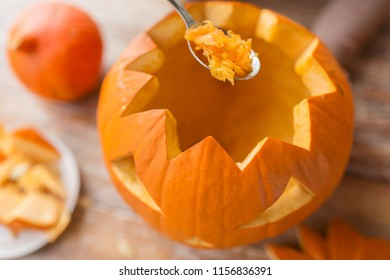halloween, decoration and holidays concept - close up of spoon carving pumpkin flesh and making jack-o-lantern at home