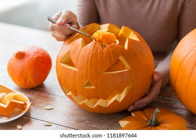 halloween, decoration and holidays concept - close up of woman with spoon carving pumpkin flesh and making or jack-o-lantern at home