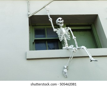 Halloween decoration human skeleton sitting on a window ledge, waving