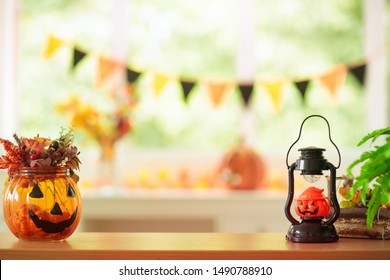 Halloween decoration. Pumpkin lantern and autumn leaf in home interior design. Festive decorated table family traditional celebration. Fall holidays. Window with banner and sun light in living room.