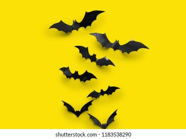 halloween decorations concept - many black paper bats on yellow background
