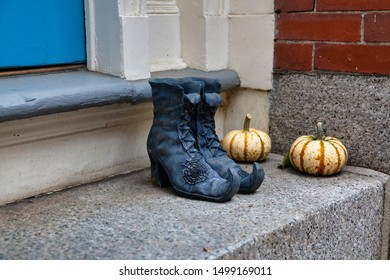 Halloween decorations on the doorstep. witch boots and pumpkins outside
