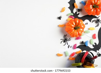 Halloween decorations on white background. Flat lay composition with orange pumpkins, sweet candies, pot, spiders, bats. Halloween holiday greeting card mockup. Top view with copy space.