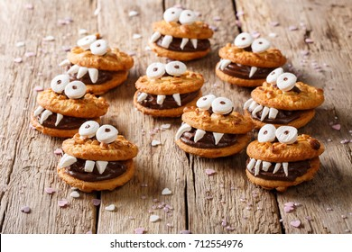 Halloween Dessert: funny monsters from cookies close-up on a table. horizontal
