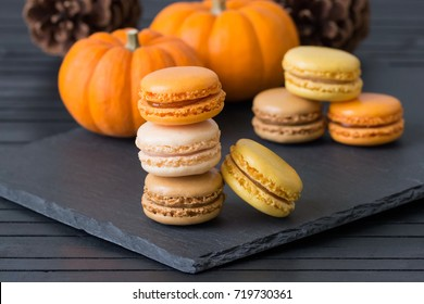 Halloween dessert. Thanksgiving menu. French macarons. Chocolate and pumpkin macaroons on the black background. Close up macarons.