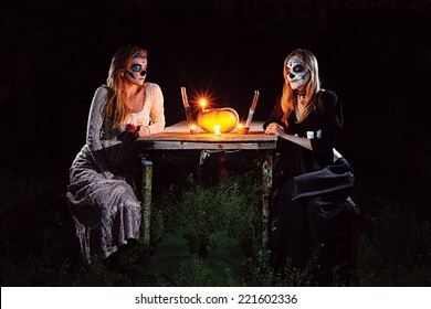 Halloween Dinner; Two Gothic looking girls with painted mask sitting at the table with a pumpkin, candles, rose and knives as if they are having a romantic dinner together