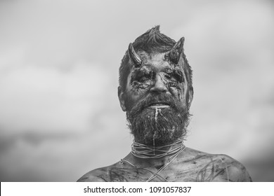 Halloween dragon creature on cloudy sky. Temptation, hell, evil, horror, darkness concept. Satan with red blood and wounds on face skin. Demon man with beard. Devil head with bloody horns
