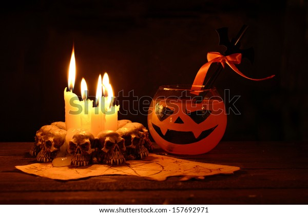 Halloween drink with evil candles on wooden table in the darkness