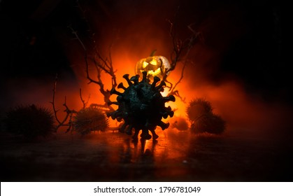 Halloween during Corona virus global pandemic concept. Glowing pumpkins and Covid novel on dark with thematic spooky decorations. Halloween pumpkin on foggy backlight. Selective focus