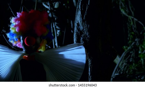Halloween, evil clown with a bow around his neck in a terrible dark forest at night. lightning flashes