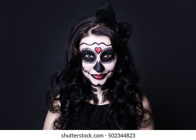 halloween face art woman with skull make up over black background