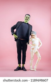 Halloween Family. Happy Father and Children Girl in Halloween Costume and Makeup. Bloody theme: the crazy maniak faces on pink studio background