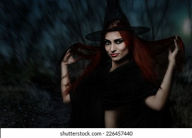 Halloween fantasy theme: redhead witch girl in forest