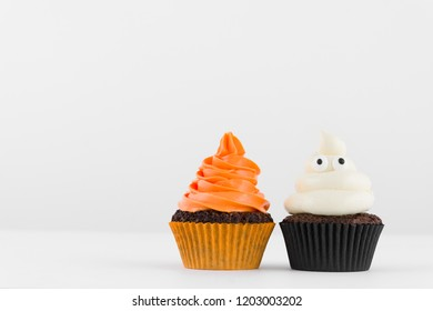 Halloween. Festive close-up view of decorative homemade Halloween white and orange frosted cupcakes with eyes on white background. Text space concept.