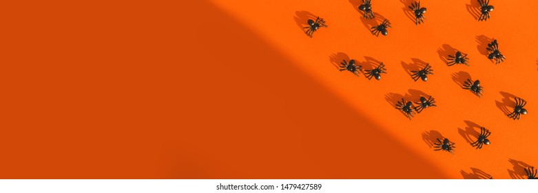 Halloween festive greeting card with spiders and shadow on a bright orange background. Postcard and scenery for All Saints Day. Top view. Flatlay. Copy space