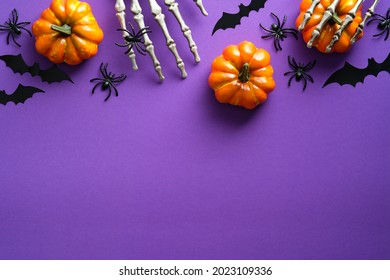 Halloween flat lay composition with pumpkins, bony hands, spiders, bats on purple background. Happy halloween banner mockup.