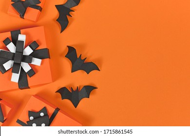 Halloween flat lay with orange, black and white seasonal paper craft gift boxes and back paper flying bats on blank background with copy space