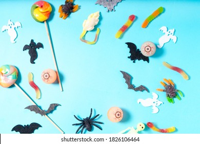 Halloween flat lay top view frame with candies on aqua blue background