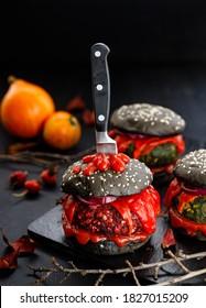 Halloween food, black burger on dark background close up view