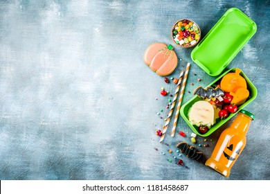 Halloween food, school lunch box with ghost sandwich, carved little pumpkins, cookies, candies and orange juice in funny monster bottle, blue concrete background top view copy space