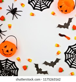 Halloween frame of scattered candy and decor. Flat lay over a white background. Copy space.