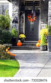 Halloween front door decorated with autumn flowers, pumpkins, a skeleton and a tombstone.