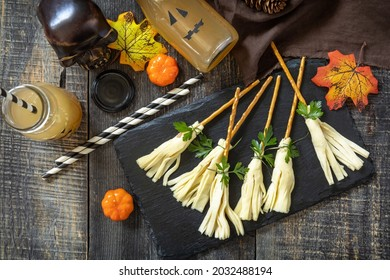 Halloween funny idea for party food. Halloween creative cheese snack on a wooden table. Top view flat lay background.