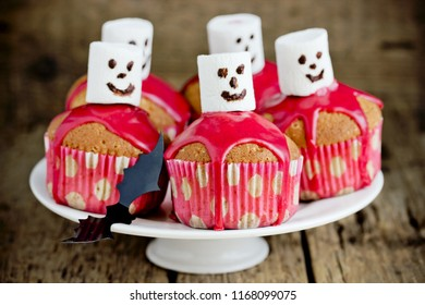 Halloween ghost cupcakes with blackberry glaze and marshmallow on wooden background