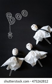 Halloween ghost lolly pops on black chalkboard.