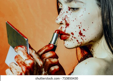 Halloween girl applying red lipstick makeup. Woman looking in pocket mirror on orange background. Model with bloody hands and blood on face. Make up and visage concept. Halloween party and holiday.