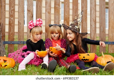 Halloween girl showing tasty treat to her friends while eating candies
