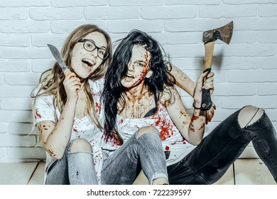 Halloween girls sitting with axe and knife on floor. Bloody women smiling on white brick wall. Happy maniacs with long hair and red blood splatters. Violence and horror. Halloween holiday concept