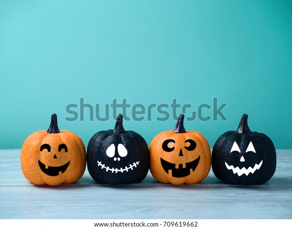 Halloween glitter pumpkin jack o lantern decor with funny faces.