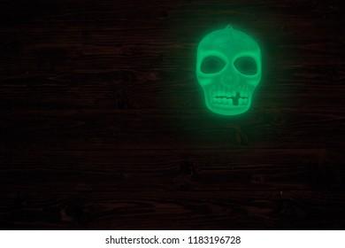 Halloween glowing phosphoric human skull over wooden table background. Neon light.