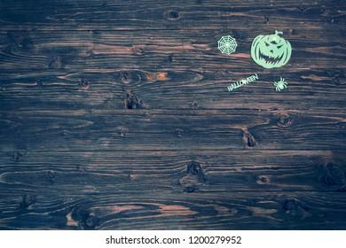 Halloween glowing phosphoric Jack-o'-lantern over wooden table background. Neon light.