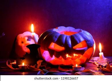 Halloween. Glowing pumpkin in dark blue light. Bat. Halloween pumpkin head jack lantern on wooden background. Autumn leaves and candles