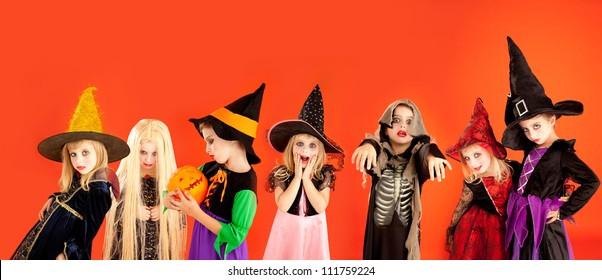 Halloween group of children girls costumes on orange background