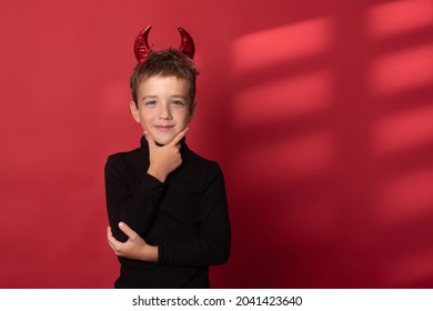 Halloween Happy child laughs out loud with devilish horns in a black turtleneck against a red studio background. Happy Halloween holidays concept.