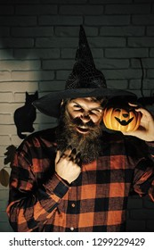 Halloween hipster with evil face in witch hat. Man with pumpkin in plaid shirt in darkness. Holiday celebration symbols on brick wall. Mystery and horror concept. Jack o lantern.