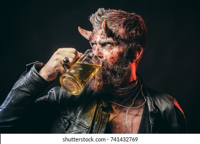 Halloween hipster with satan horns hold glass mug. Devil with red blood and wounds on face. Holiday celebration and party. Bad habits and addiction concept. Man demon drink beer on black background.