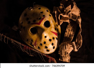 The Halloween Hockey mask of dead. Put on the table in the dark horror environment, with bandage and old rusty blade.