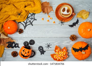 Halloween holiday background with coffee cup, pumpkin and autumn leaves on wooden table. Top view from above. Flat lay