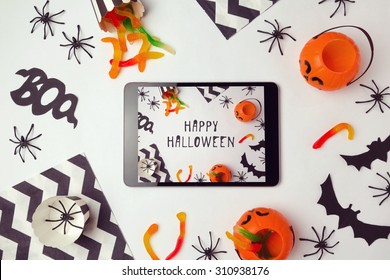 Halloween holiday background with digital tablet and decorations