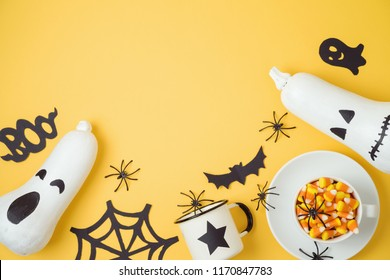 Halloween holiday background with jack o lantern pumpkin, candy corn and decorations. View from above. Flat lay