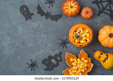 Halloween holiday background with jack o lantern pumpkin, candy corn and decorations on blackboard. View from above. Flat lay
