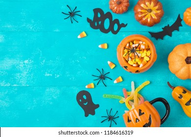 Halloween holiday background with jack o lantern pumpkin, candy corn and decorations on blue wooden board. View from above. Flat lay