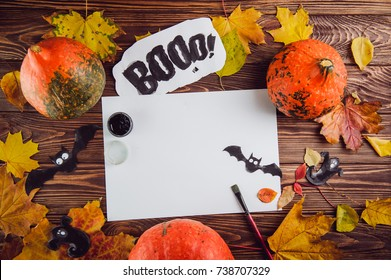 Halloween holiday background. Prepearing for party. Fresh pumpkins, coloured leaves, art, craft and painting materials on dark wooden table. Selective focus, top view. Space for text